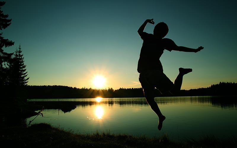 Hoppende gutt i solnedgang