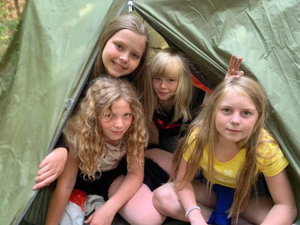Fire venninner sitter i teltet sitt
