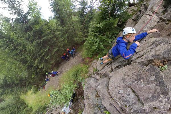 Gutt som klatrer i fjellvegg.